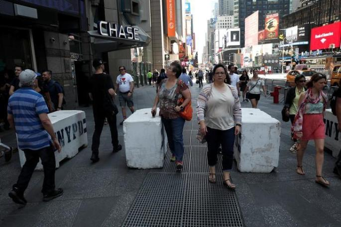 People walk between newly erected concrete barricades outside the 3 Times Square building in Times Square where a speeding vehicle struck pedestrians Thursday in New York City